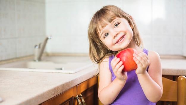 Portrait eines lächelnden mädchens, das in der küche anhält frischen roten apfel steht