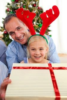 Portrait eines lächelnden vaters und seiner tochteröffnung weihnachtsgeschenke