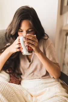 Portrait eines Mädchens, das Kaffee vom Becher trinkt