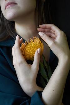 Portrait eines mädchens, das einen orange protea anhält