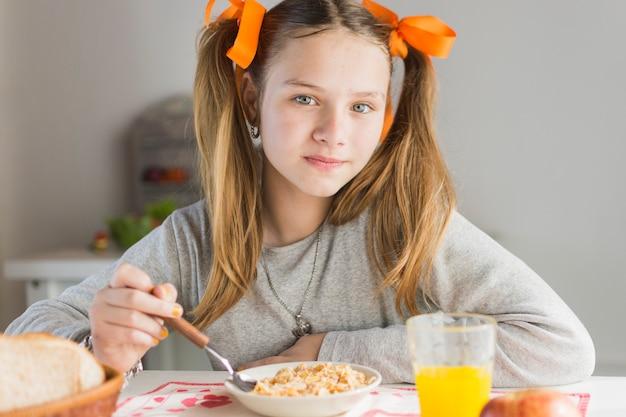 Portrait eines mädchens, das gesunde getreide mit glas saft auf tabelle isst