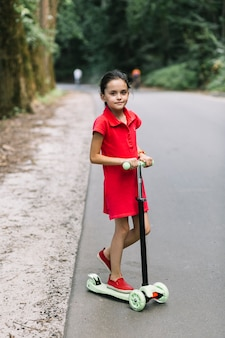 Portrait eines mädchens, das über roller auf straße steht
