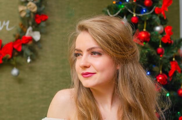Portrait eines mädchens mit leuchtend roten lippen, blondes langes haar junges mädchen in einem weißen warmen mantel, schultern sind sichtbar. ferien. fröhliche weihnachten