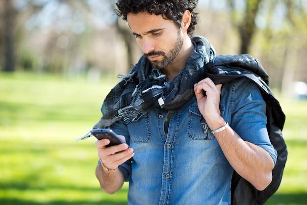Portrait eines mannes, der seinen handy in einem park verwendet