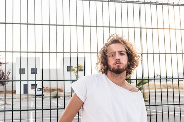 Portrait eines mannes, der vor zaun steht