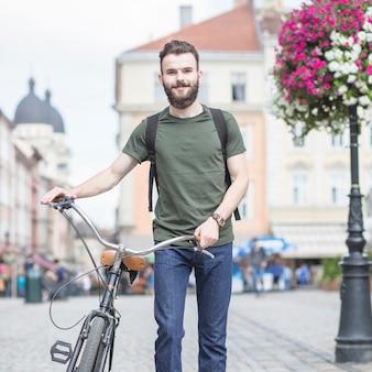 Portrait eines Mannes mit dem Fahrrad, das in Stadt geht