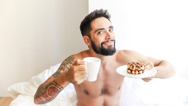 Portrait eines mannes mit tasse kaffee und waffel auf platte