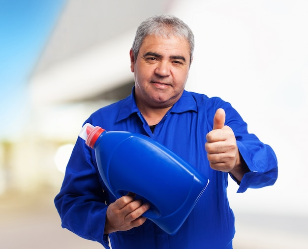 Portrait eines mechanikers eine ölflasche hält