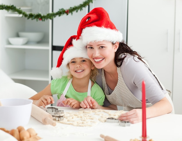 Portrait eines netten mädchens mit ihren mutterbacken weihnachtsplätzchen