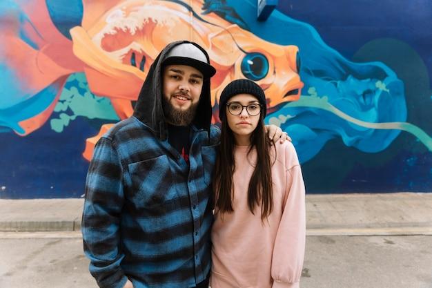 Portrait eines paares vor graffitiwand