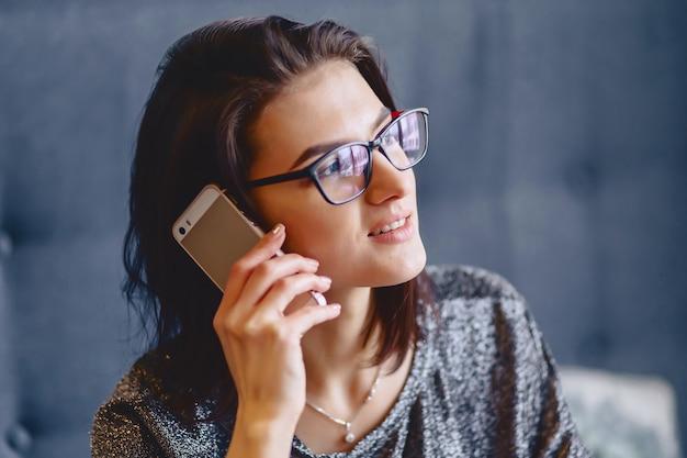 Portrait eines reizend mädchens in den gläsern mit einem telefon