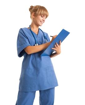 Portrait eines schönen krankenschwesterschreibens auf einem klemmbrett