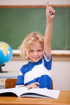 Portrait eines schülers, der seine hand anhebt