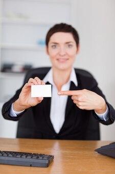 Portrait eines secretertary, das auf eine unbelegte visitenkarte zeigt