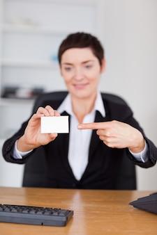 Portrait eines secreterty, das eine unbelegte visitenkarte zeigt