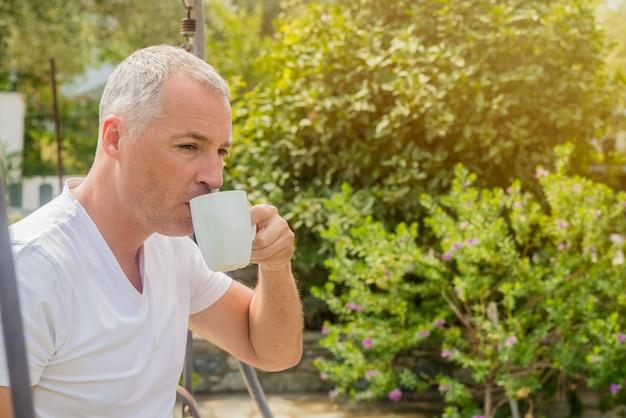 Portrait eines selbstbewussten geschäftsmannes sitzt auf der bank und trinkt kaffee im freien. geschäftsmann trinkt kaffee im garten. vintager ton