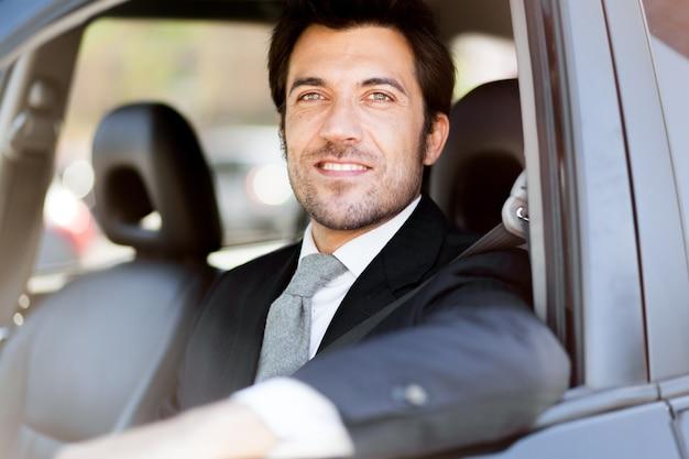 Portrait eines stattlichen lächelnden geschäftsmannes, der sein auto antreibt