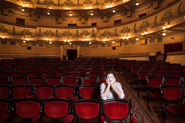Portrait eines weiblichen pantomimen, der auf stuhl sitzt