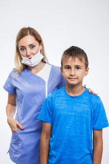 Portrait eines weiblichen zahnarztes und des jungen auf weißem hintergrund