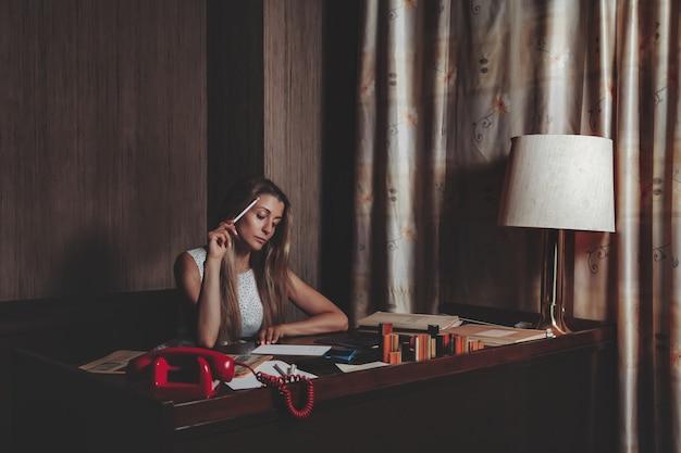 Portrait emotion erwachsene frau schauspielerin mit alten zeitungsarbeit gekleidete retro-styling-kleidung im vintage-büro. frau im pin-up-mode-stil schwarz-weißes kleid in polka dot funktioniert abend