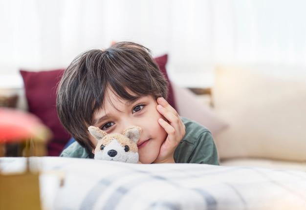Portrait gesundes kind, das kamera mit lächelndem gesicht betrachtet, das auf sofa im wohnzimmer liegt, kinderjunge mit glücklichem gesicht, das mit entspannen zu hause im sonnigen tag frühling oder sommer spielt, positives kinderkonzept