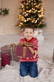 Portrait glücklich lächelnder kleiner junge im roten strickpullover mit weihnachtsgeschenkbox nahe baum