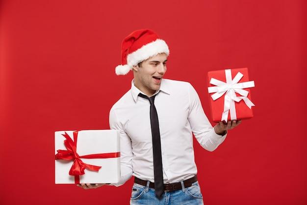 Portrait glücklicher sankt-weihnachtsgeschäftsmann, der mit seinem geschenk über rotem hintergrund aufregt.