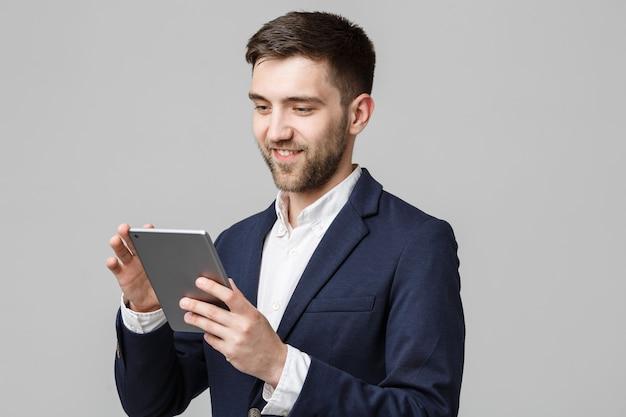 Portrait handsome business-mann, der digitales tablett mit lächelndem selbstbewusstem gesicht spielt