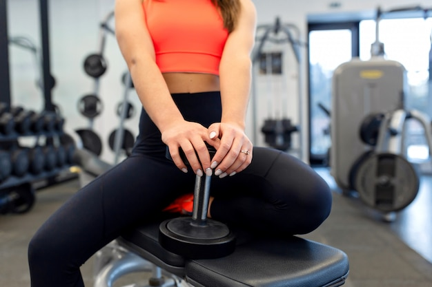 Portrait hübsche fit frau, die hanteln auf bank im fitnessstudio anhebt
