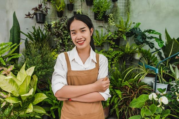 Portrait junge asiatische gärtnerin mit schürzenständer und kreuzarm, sie lächelt und schaut zur kamera