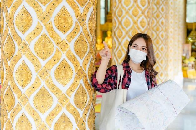 Portrait junge asiatische rucksacktouristin in maske, die am schönen thailändischen tempel steht und papierkarte in der hand hält, sie zeigt und freut sich looking