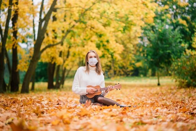 Portrait junge frau in der schutzmaske, die ukulele-gitarre im herbstpark, gesundes reisekonzept des lebensstils spielt