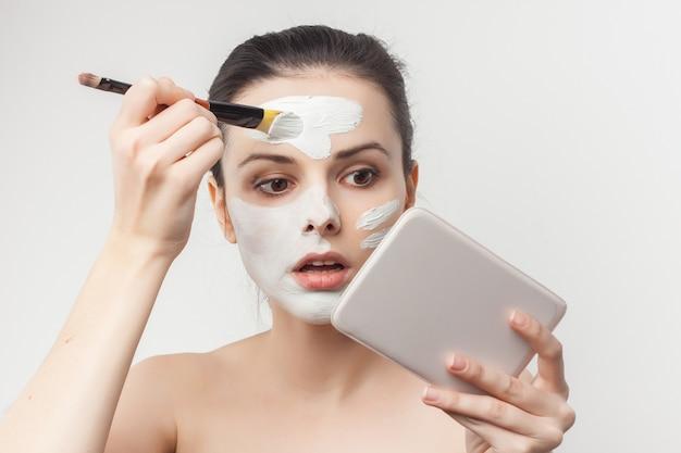 Portrait junge schöne frau, die eine gesichtsmaske mit einem pinsel mit einem spiegel in der hand anwendet