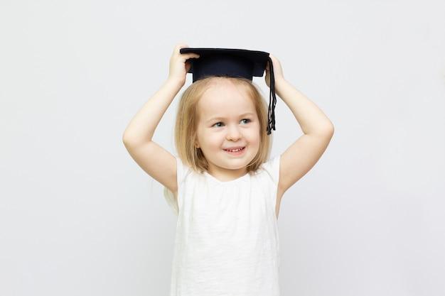 Portrait kleines mädchen trägt graduierten hut und lächelt mit glück mit kopienraum für bildungskonzept