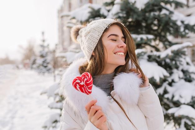 Portrait lustige erstaunliche frau, die winterzeit genießt, lollypop auf straße haltend. helle glückliche gefühle der jungen frau in der warmen weißen winterkleidung mit geschlossenen augen, großes lächeln.