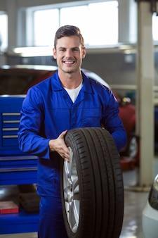 Portrait mechaniker einen reifen hält