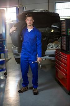 Portrait mechaniker hält reifen und lungenschlüssel