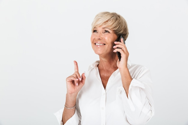 Portrait nahaufnahme einer lächelnden erwachsenen frau mit kurzen blonden haaren, die mit dem finger nach oben zeigt und auf dem handy spricht, isoliert über der weißen wand im studio