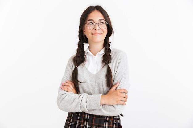 Portrait nahaufnahme eines schönen teenager-mädchens mit brille und schuluniform, das in die kamera lächelt, die über weißer wand isoliert ist?