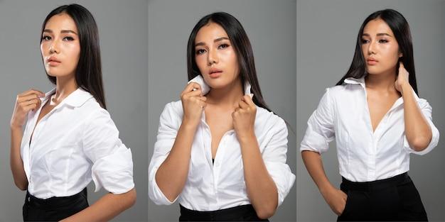 Portrait of fashion 20s asian woman hat schöne schwarze lange glatte haare, sie trägt ein weißes hemd blick in die kamera über grauem hintergrund isoliert