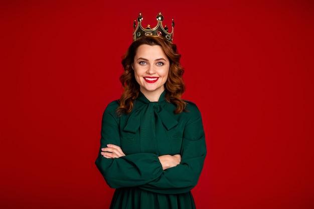 Portrait ofattractive tragende krone verschränkte arme auf rotem hintergrund
