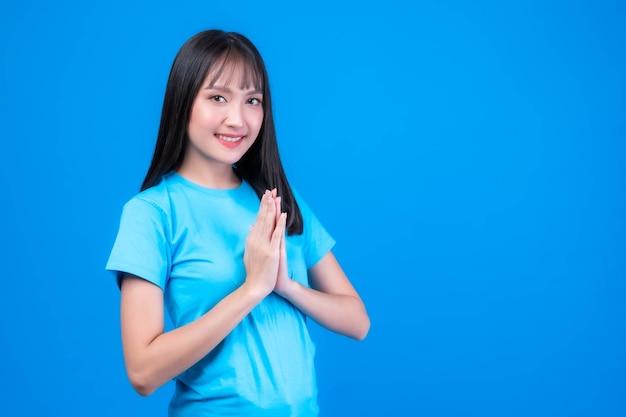 Portrait schöne asiatische junge frau knallt frisur respekt, sawasdee symbol aus thailand grußkultur für hallo oder auf wiedersehen einzeln auf blauem hintergrund
