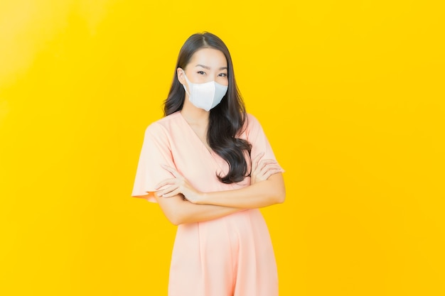Portrait schöne junge asiatische frau mit maske zum schutz des covid19-virus auf gelber wand