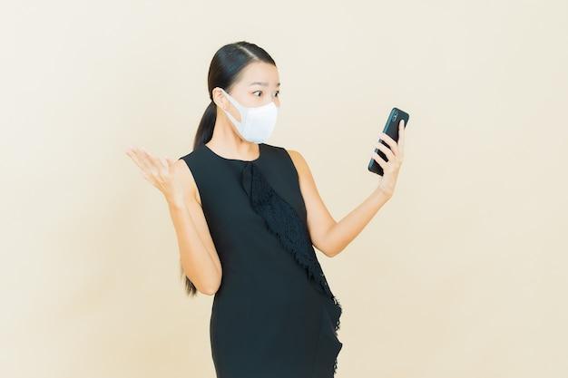 Portrait schöne junge asiatische frau mit maske zum schutz von covid19 oder virus auf gelber wand