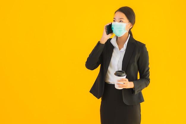Portrait schöne junge geschäft asiatische frau tragen maske verwenden handy mit kaffee