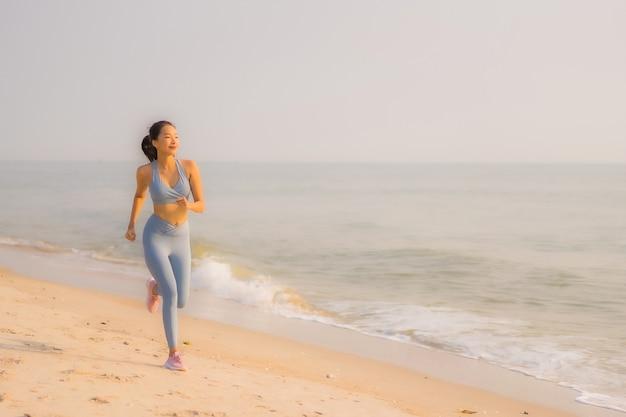 Portrait sport junge asiatische frau bereiten übung vor oder laufen auf dem strandmeerozean