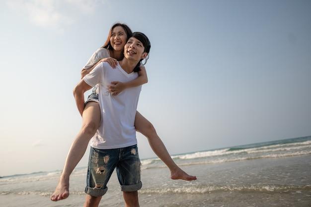 Portrait verliebtes paar am strand sommerferien fröhliches mädchen auf jungem freund, der spaß hat sommer