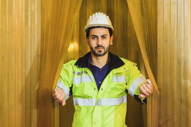 Portrait vertrauen hübscher lateinischer ingenieur arbeiter mann öffnet gelben pvc-vorhang in einer lebensmittelfabrik