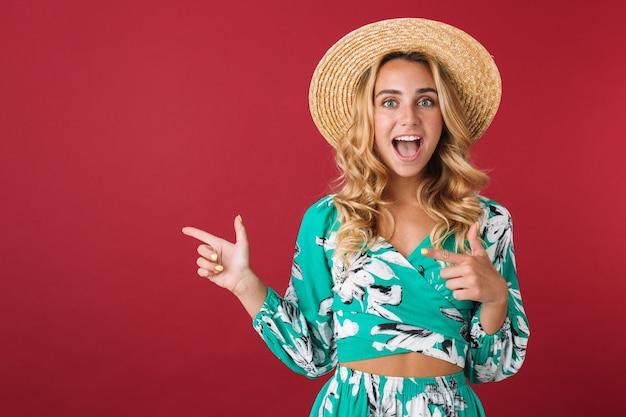 Portrait von cutie glücklich lächelnde junge schöne blonde süße frau im kleid posiert isoliert über roter wand zeigend