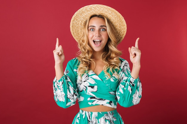 Portrait von cutie schockiert schreiend lächelnde junge schöne blonde süße frau im kleid posiert isoliert über roter wand zeigend